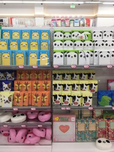 A retail display of Daiso notebooks with animal illustrations on the covers.