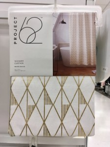 Shower curtain with gold diamond pattern on cream background, folded up and hanging for display in a Target store.
