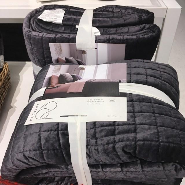 Gray velvet quilt, folded up for sale at a Target store