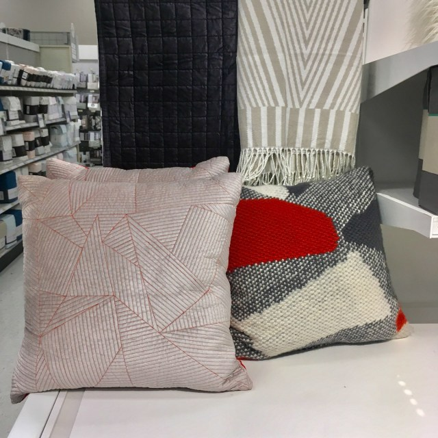Display of quilts and throw pillows at Target. One quilt has a square pattern, the throw has a diamond pattern, one throw pillow has textured lines, and another throw pillow has a chunky knit texture.