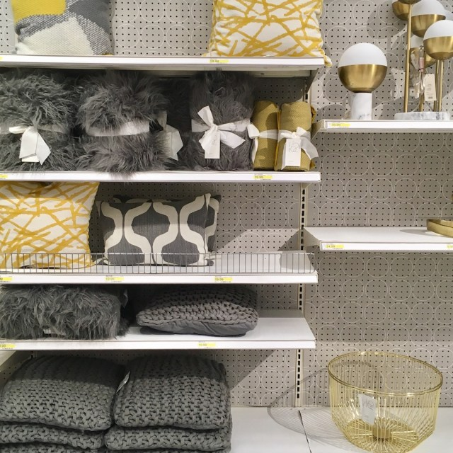 Shelves with black and yellow colored pillows, throws, and other decor
