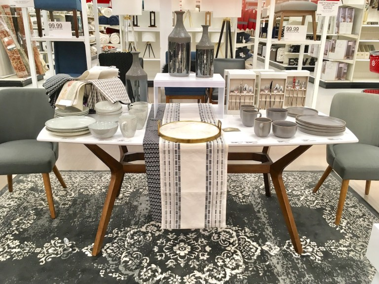 White dining table with medium brown legs at an angle
