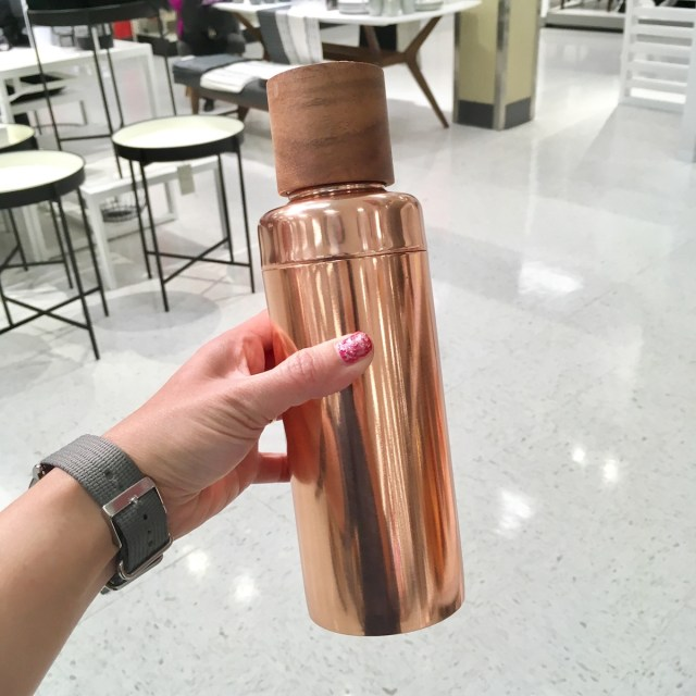 Hand holding a tall coctail shaker in rose gold color.