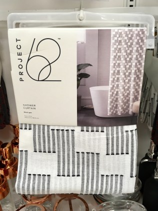 Black and white rectangular shower curtain, as shown folded up and hanging on a hanger in a store.