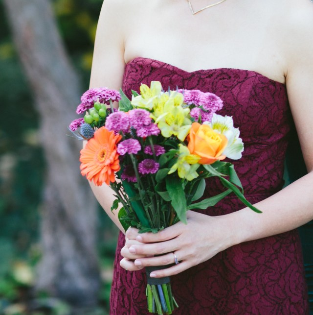 Close up of bouquet in purple, pink, orange, with two hands holding it.