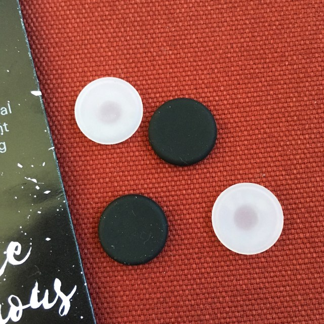 Four Holé button covers. They are made of silicone. Two are black, two are transparent-ish.