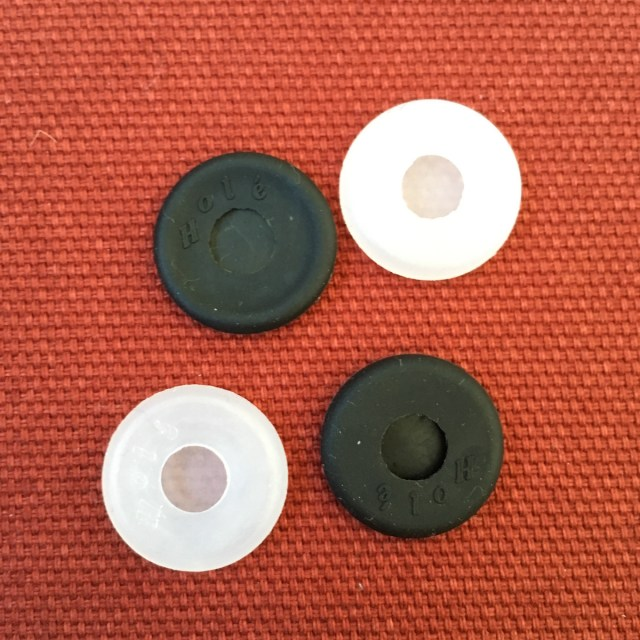 Holé button cover as shown from the back. There are four, two in black, two transparent.