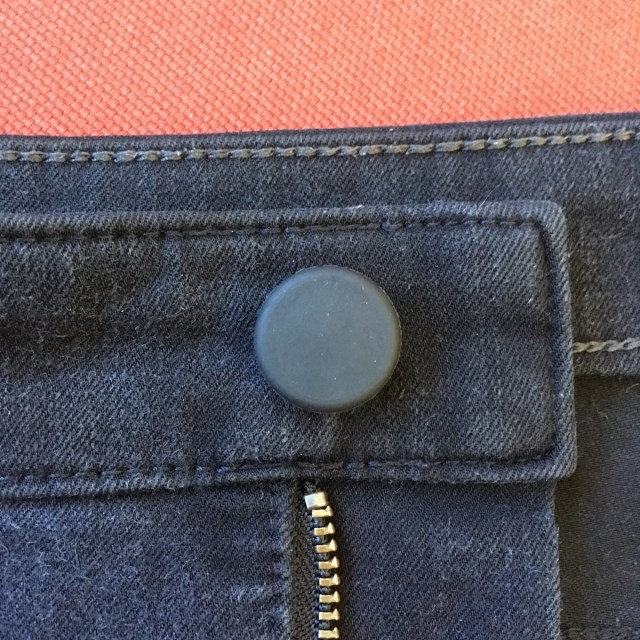 Closeup of fly of black pair of jeans with a Holé button cover.