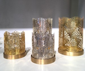 Candle holders with elaborate lazer cut patterns. They are made out of metal. Some are silver in color and some are gold.