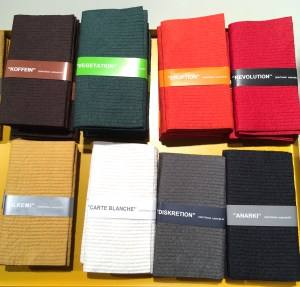 Eight stacks of kitchen towels in various colors, including brown, dark green, orange, red, sand, white, gray, and black.