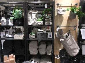 Shelving with a display of porganizing pouches. The pouches are collapsible. The ones on display have been opened up and have plants and other items in them.