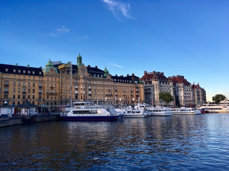 A view of buildings in Stockholm. They are about 7 to 8 stories tall, with ornate architecture, and by a body of water. There are small boats docked in the water.