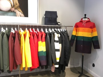 Store display at Stutterheim. A rainbow patterned rain coat is on a dress form, and is next to a rack of rain coats. There is also a backpack on a shelf.