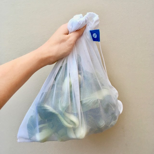 A hand holding a white mesh produce bag filled with a pound of bok choy.