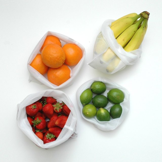 Four mesh produce bags filled with produce, as seen from above. The tops of the bags are open.