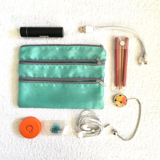 A pouch with three zippered comparments and the items stored inside the pouch laid out around it, including a purse hook, phone charger, earplugs, headphones.