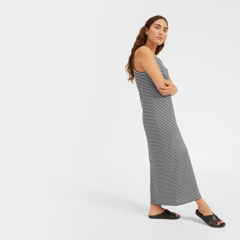 A model, a white woman with long brown wavy hair, wears an Everlane cotton tank dress in black and white stripes.
