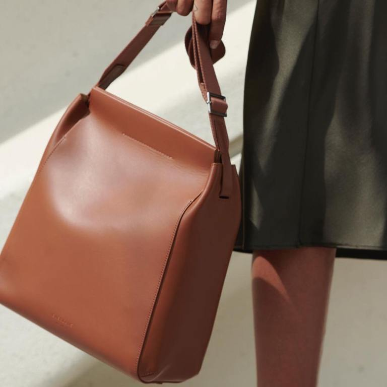 A hand holding a brown square-shaped leather bag.