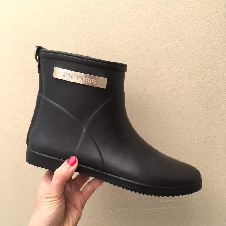 338205b35 A hand with red nail polish holds up a black rain boot. There is a