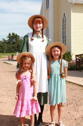 This is a photo of Anne Shirley of Green Gables with two little girls.