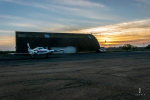 small airport hangar in the sunset