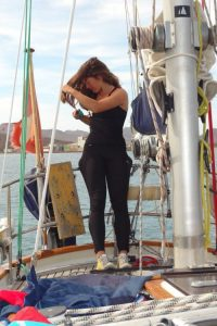 Girl brushing her hair at the back of a sailing boat