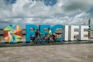Cyclists posing in front of the Recife letters