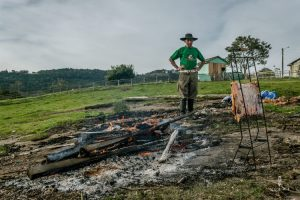 Gaucho preparing a costilla next to a camp fire