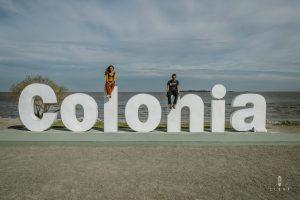 Tourists sitting on Colonia letters in Colonia del Sacramento