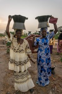 Women in Senegal posing with a cooking stove balancing on their head