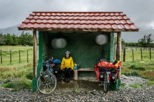 Cyclist hiding for the rain in a bus stop on the carretera austral