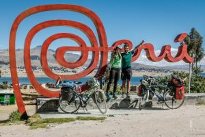 cyclists posing in front of peru letters