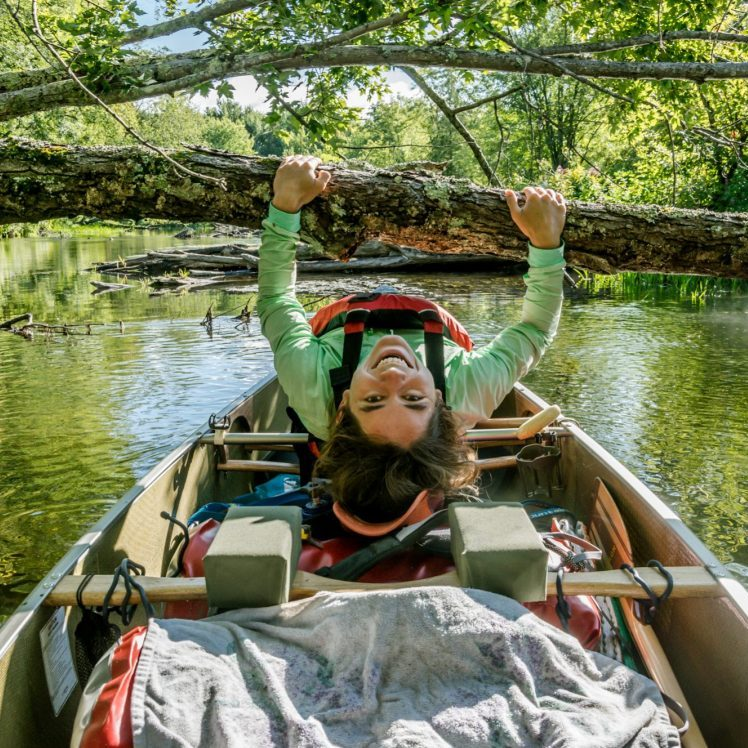 canoeing under fallen tree on the canoe parcours