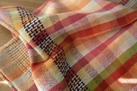 A tea towel on a table with warp and weft striping creating 1x1 squares of faux plaid. Dark brown huck panel at the front hem.