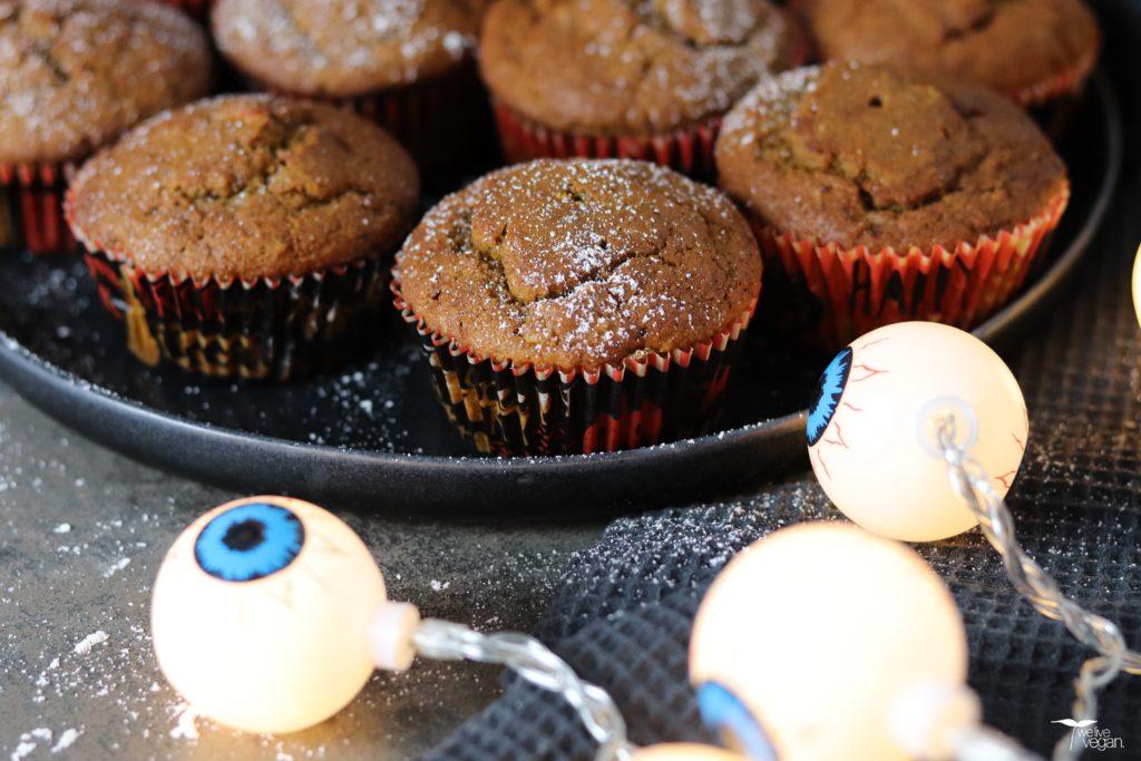 Kürbis Muffins auf einem Teller, der von einer schaurigen Halloween Lichterkette beleuchtet wird.