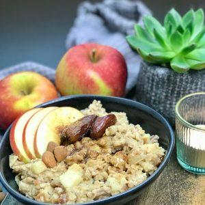 Schüssel mit Veganer Apfel Porridge zur Deko Äpfel und Datteln