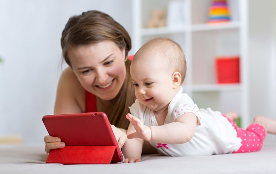 Family - mother and baby with tablet pc on floor at home. Woman and child girl relaxing at tablet computer.