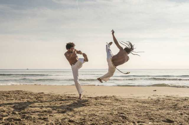 two men doing capoeira by the beach | types of martial arts | how many types of martial arts are there