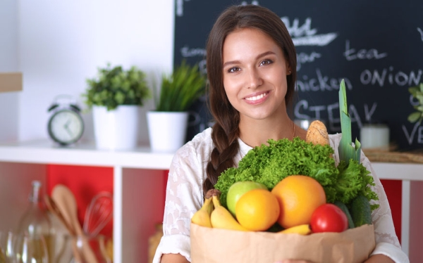 48209662 - young woman holding grocery shopping bag with vegetables .