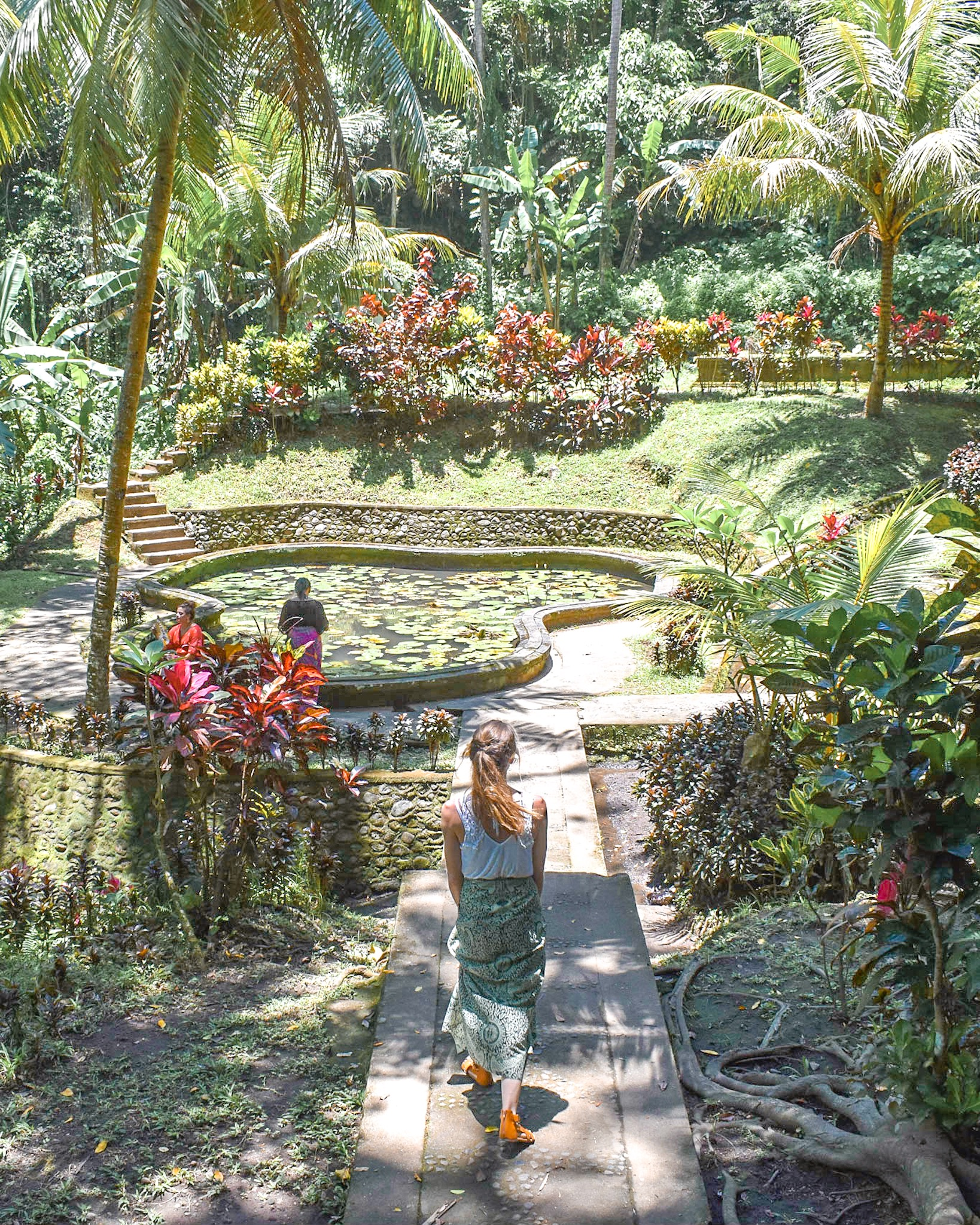 Woman Walks Out to Garden at Elephant Cave Temple in Bali