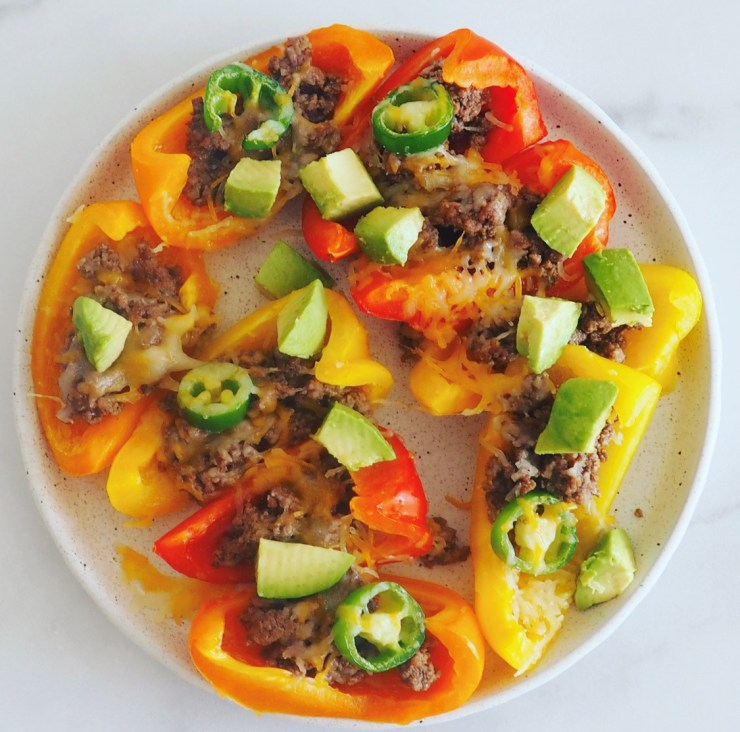 sliced bell peppers topped with ground beef, cheese, avocados, and jalapeno peppers