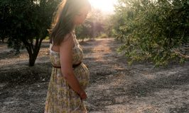 pregnant woman wearing beige and red floral sleeveless dress standing near plant