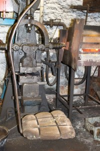 The hydraulic hammer than beats the red-glowing steel into shape. Notice the clever swinging seat that allows the operator to move between forge and hammer with little effort.