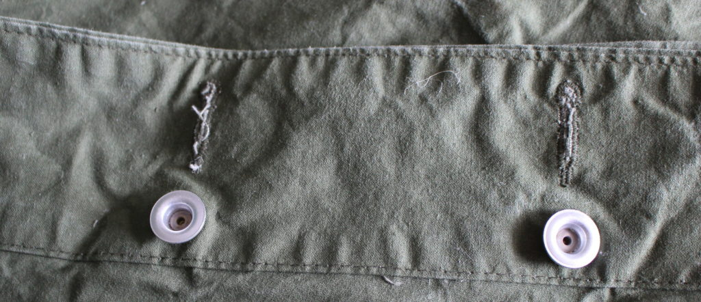 The aluminium buttons have a half on each side of the fabric, held together with a rivet.