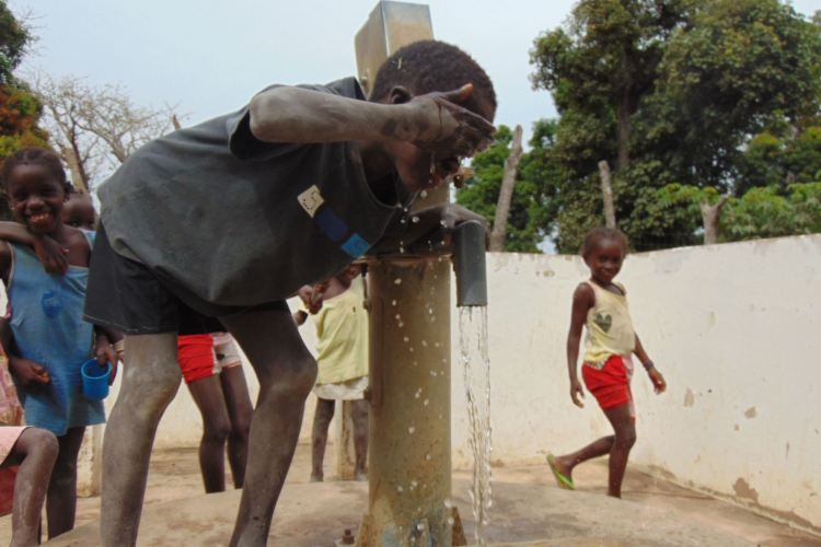 Young boy drinking from WellFound well on World Water Day