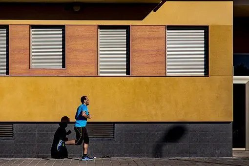 blog picture of man jogging by a building