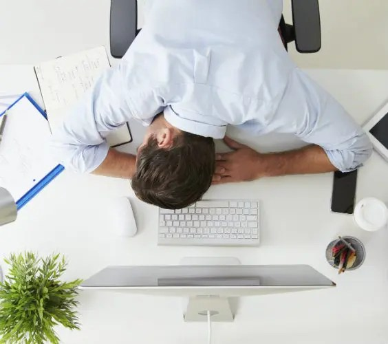 man at office desk tired