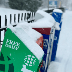 Snow covered newspaper boxes
