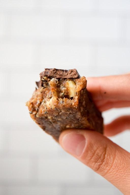 a close-up of a dark chocolate almond date bar