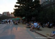 Crowds of people relaxing in the early evening sun.